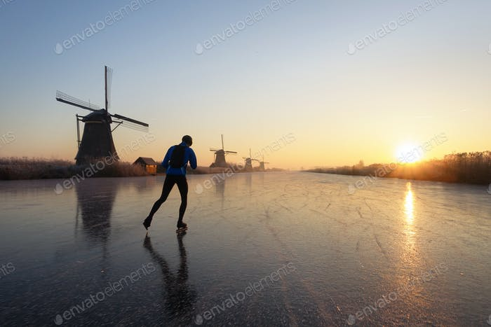 Sports person ice skating at sunrise in the Netherlands