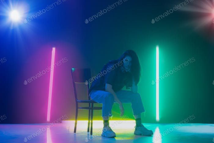 Thumbnail for Young caucasian girl posing stylish in neon light on dark background