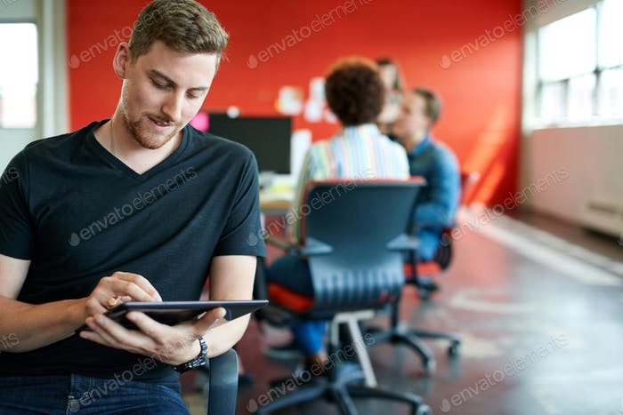 Confident male designer working on a digital tablet in red creat