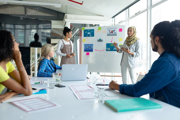 Mixed-race businesswoman in hijab giving presentation on flip chart during meeting