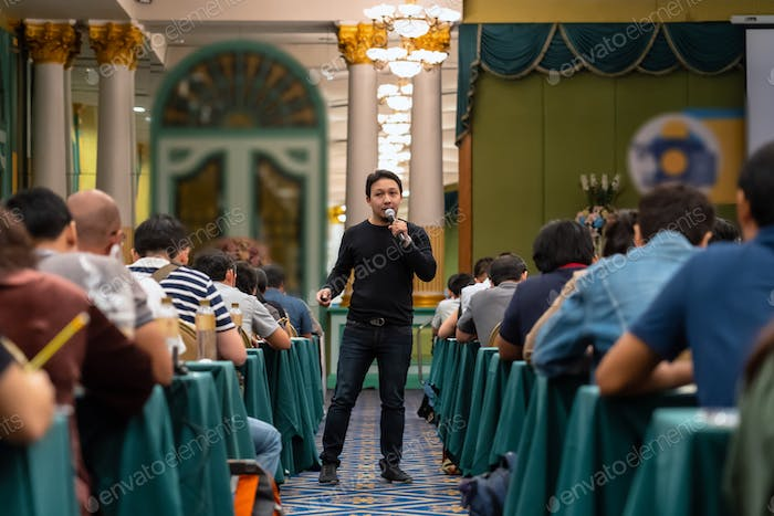 Asian Speaker with casual suit standing and giving the knowledge with audience