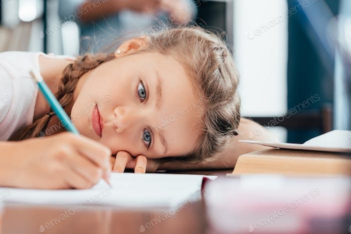 sad little girl writing homework
