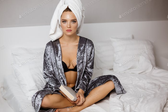 Beautiful young woman in lingerie and robe sitting in bed with towel on head and book in hands