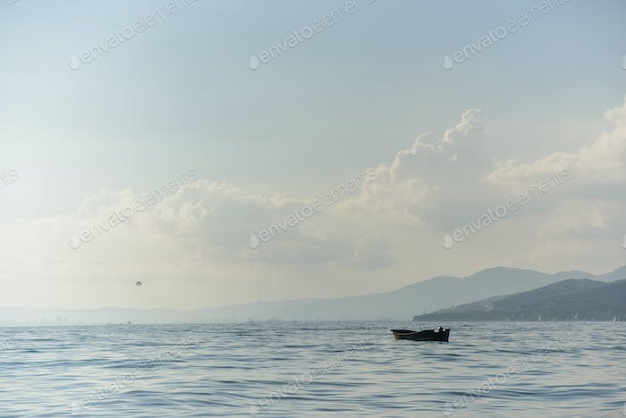 wooden boat with no people in bay sea with sky and mountain background