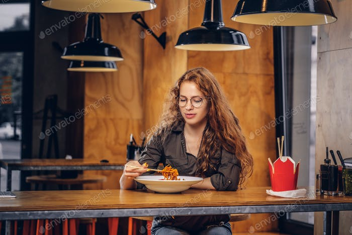 Young smart curly girl student sitting at a table in the college canteen during a break.