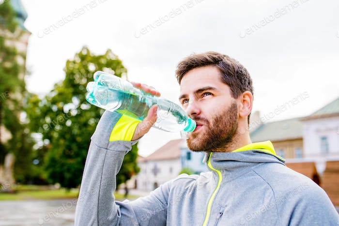 Young hipster runner in town with water bottle, drinking