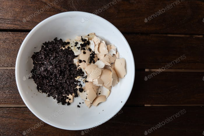 Overhead view of crushed egg shell and spent coffee grounds in bowl. Natural organic fertilizers for
