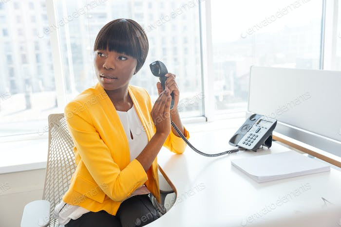 Businesswoman covering microphone on phone