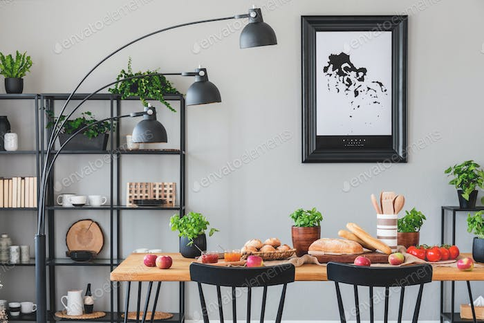 Black lamp above wooden table with eco food in grey dining room