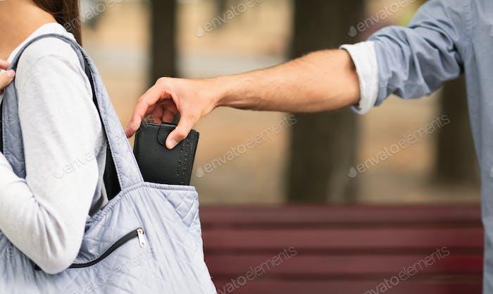 Taschendieb Dieb stehlen Geldbörse aus Frau Handtasche