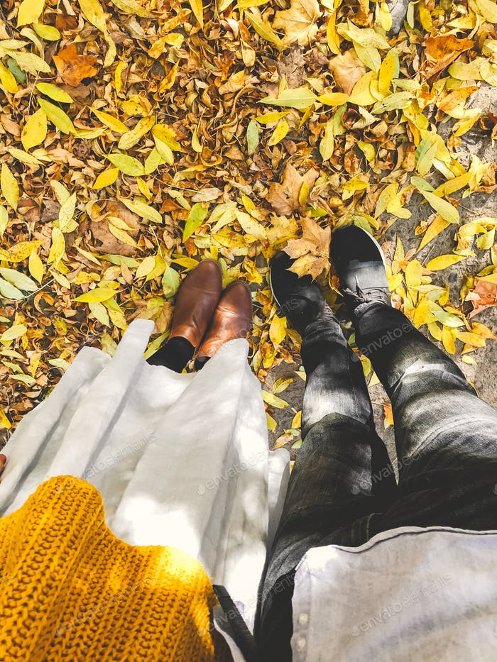 Top view of couples feet in yellow autumn leaves