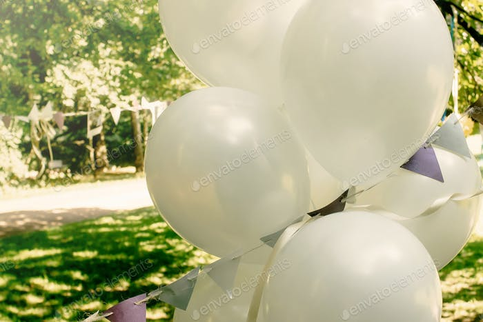 white big balloons with garland outdoors, adorning and arrangement at celebration events
