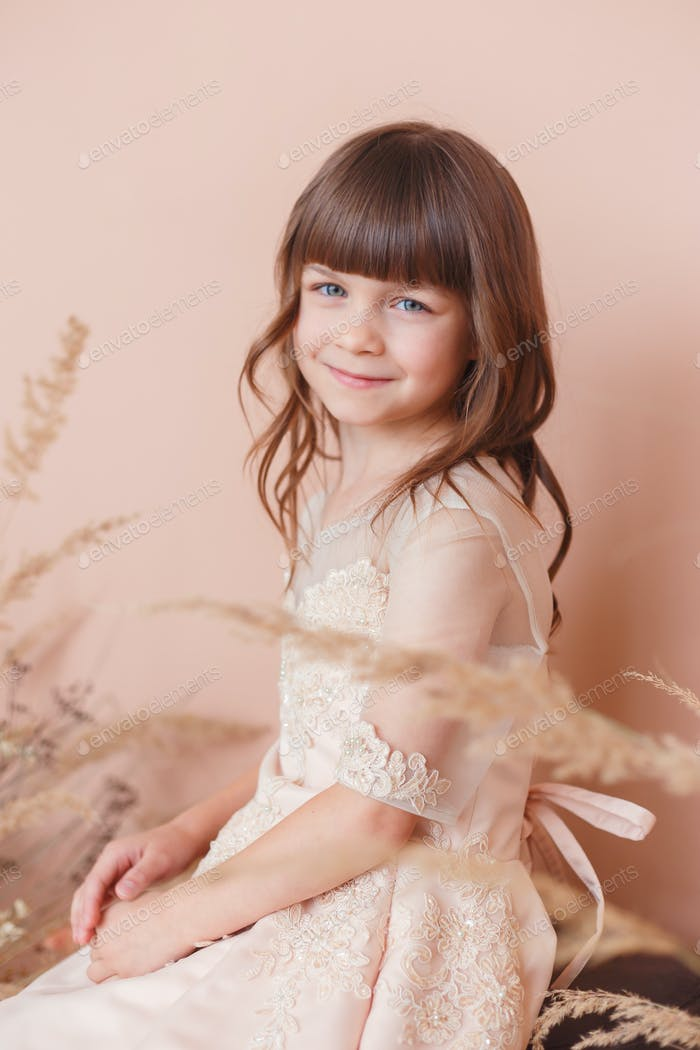 Young model girl in beige dress smiling on pastel color background