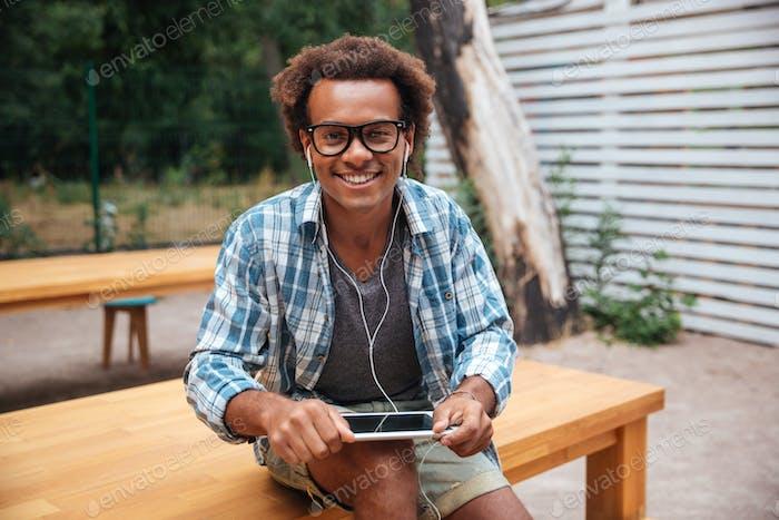 Glückliche afrikanische junge Mann mit Tablette im Park