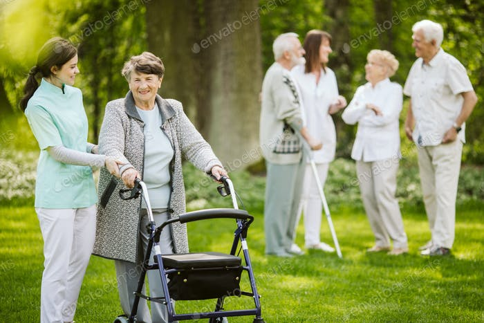 Group of senior patients with caregiver in the garden of nursing home