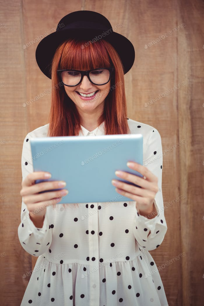 Smiling hipster woman using her tablet against wooden background