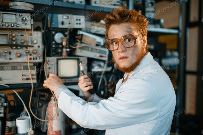 Strange engineer holds electric tube in laboratory