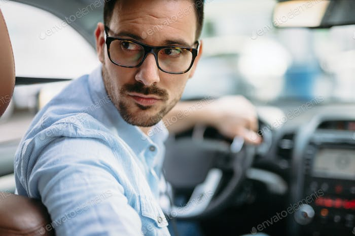 Portrait of a handsome businessman driving car