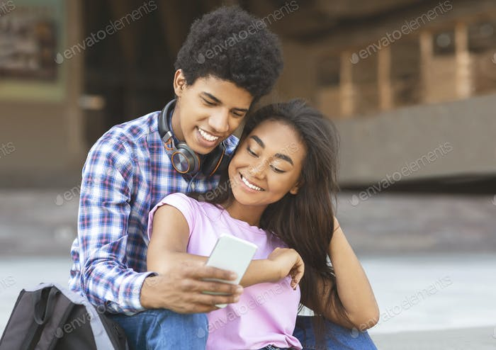 Smiling students scrolling photos in smartphone together sitting outdoors