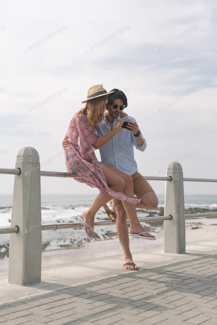 Side view of young Caucasian couple reviving photos while sitting at railing on beach on a sunny day