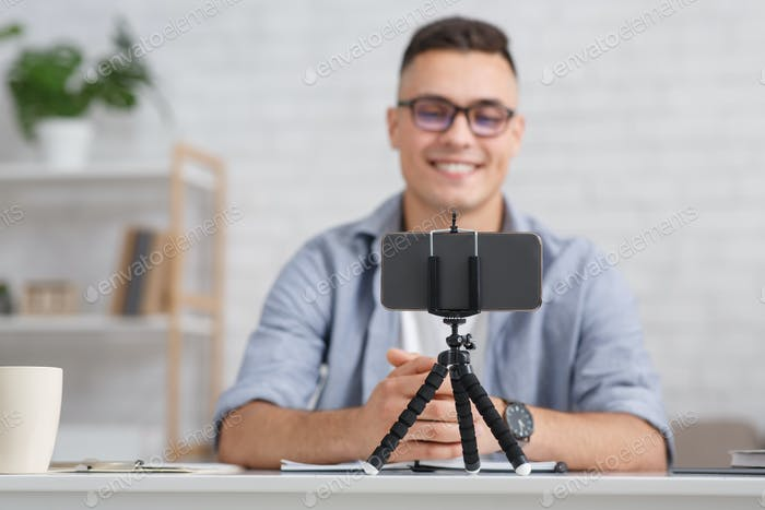 Modern hobby and remote work online. Focus on smartphone on tripod and smiling guy with glasses