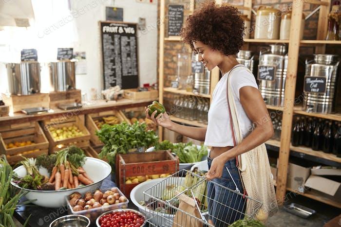 Frau Kauf von frischem Obst und Gemüse in nachhaltigen Kunststoff Free Lebensmittelgeschäft
