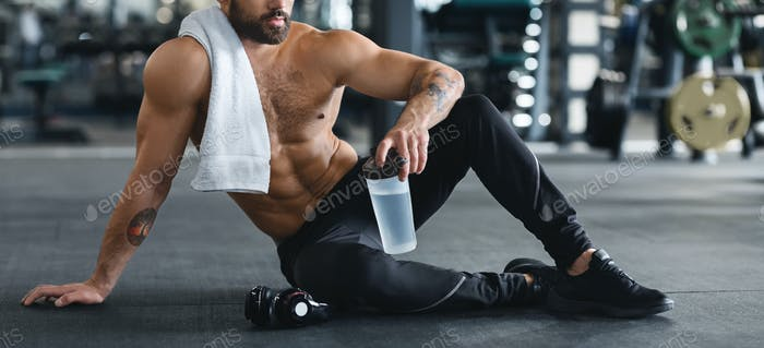 Naked man holding water bottle, sitting on floor at gym