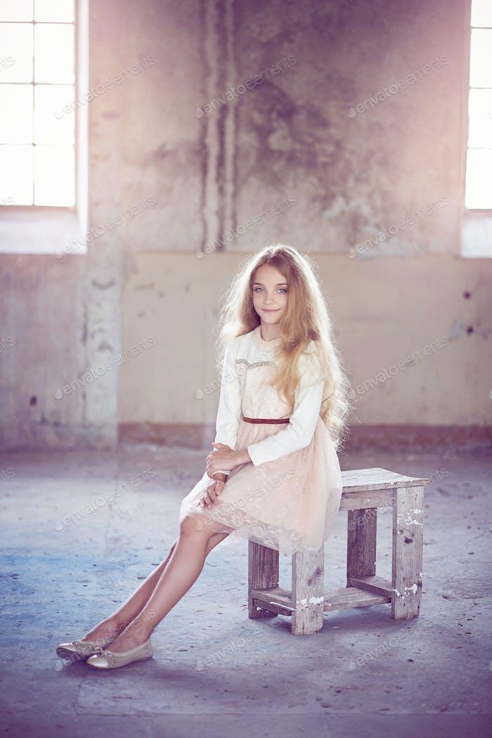 Charmantes kleines Mädchenmodell sitzt in einem Holzstuhl in einem Studio.