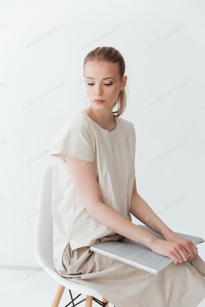Concentrated blonde lady sitting indoors reading book.