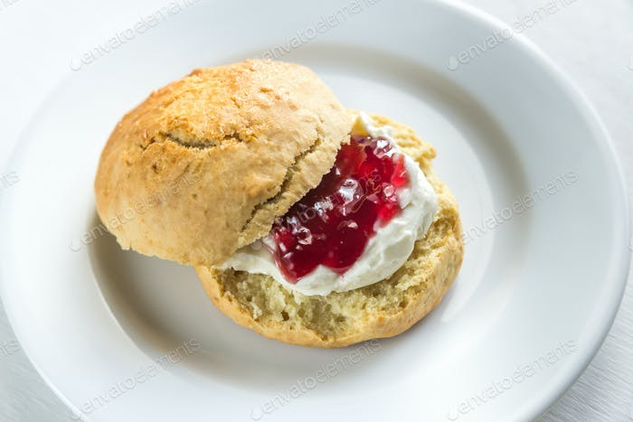 Scone with cream and cherry jam on the plate