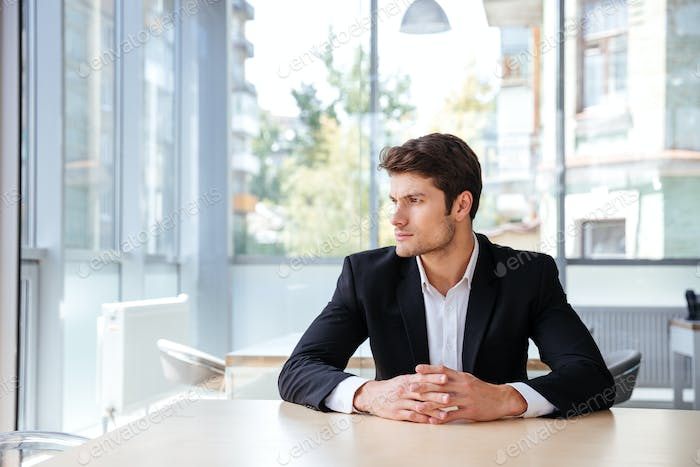 Pensive young businessman sitting and thinking in office