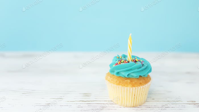 Birthday greeting concept. Yellow candle on muffin, cupcake. Blue background
