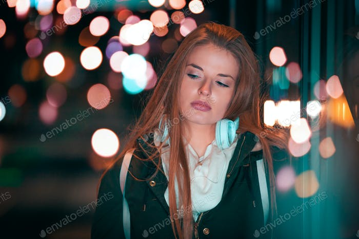 Beautiful woman at night in the city among colorful lights