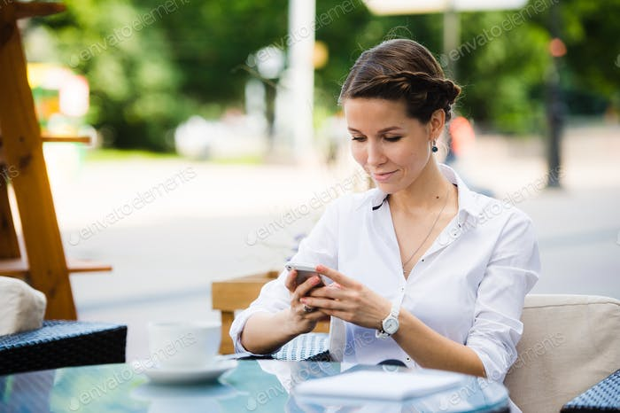 Portrait of a charming business woman chatting on her smart phone while waiting someone in cafe