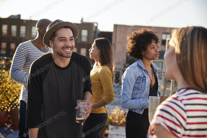 Friends talking at a party on a New York rooftop, close up