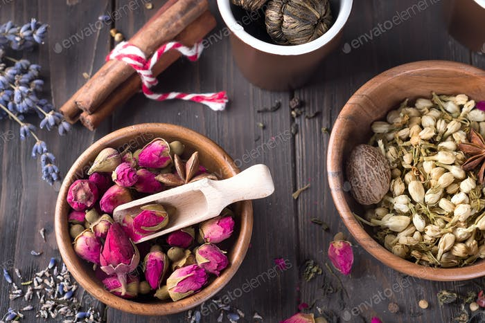 Dried rose bud in wooden bowl, which are used for making tea on wooden background. Flat lay