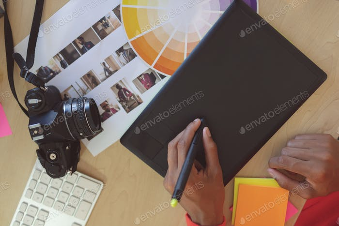 Young female graphic designer using graphic tablet at desk