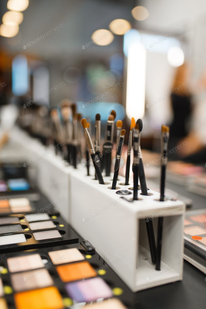 Shelf with shadows and brushes in cosmetics store