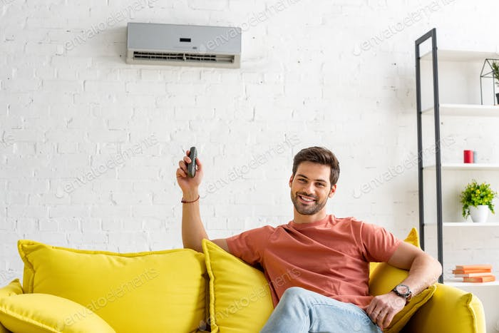 handsome man looking at camera while sitting under air conditioner and holding remote control