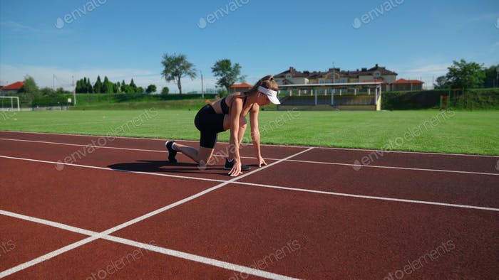 Woman practicing sprinter position at stadium