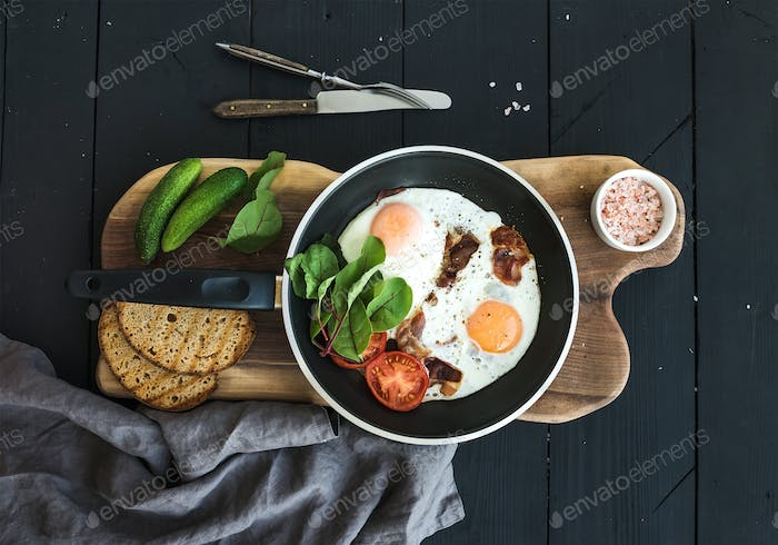 Pan of fried eggs, bacon, tomatoes with bread, mangold and cucumbers