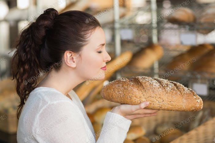 Ziemlich Brünette riechen Laib Brot bei die Bäckerei