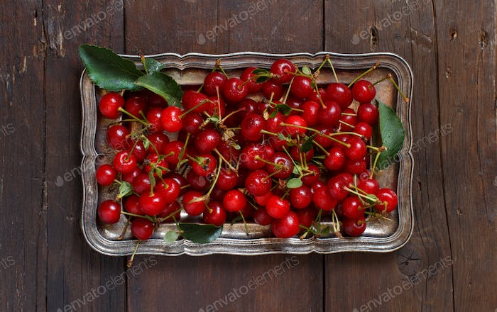 Fresh sour cherries on a tray on a wooden table