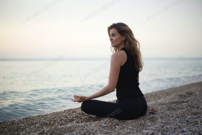 young beautiful woman meditates while sitting by the sea