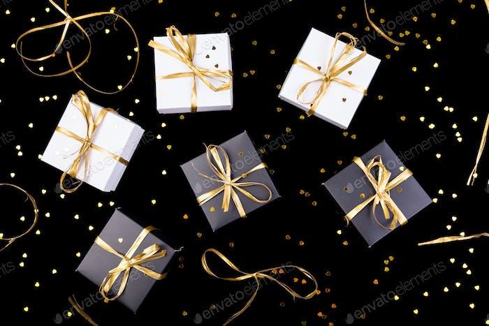 Schwarz-weiße Geschenk-Boxen mit goldenem Band auf glänzendem Hintergrund. Flache Lag.