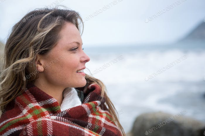 Happy woman wrapped in shawl looking around