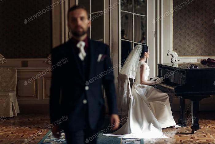 elegant gorgeous bride playing the fortepiano and stylish handsome groom posing