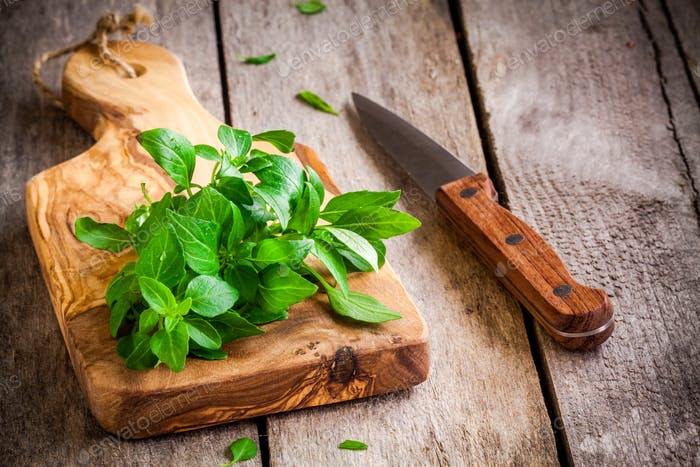 bunch of fresh organic basil in olive cutting board with knife