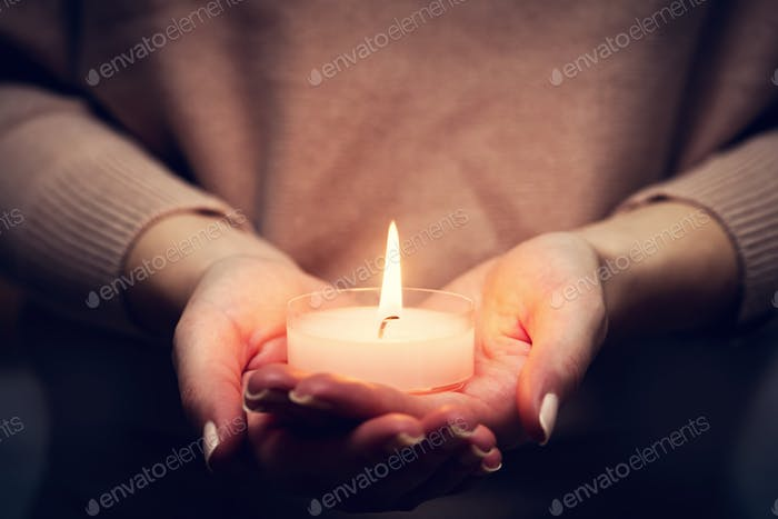 Candle light glowing in woman's hands. Praying, faith, religion