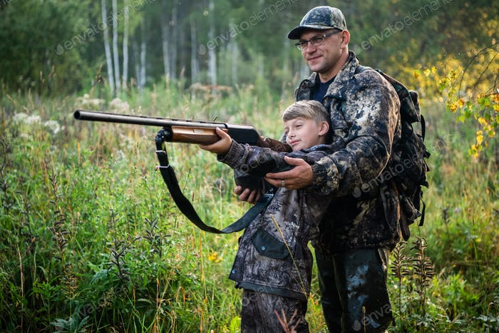 Father teaching his son about gun safety and proper use on hunting in nature